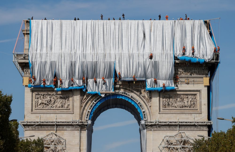Workers install a shimmering wrapper to envelop Paris landmark, the Arc de Triomphe, in a posthumous installation by artist Christo on the Champs Elysee avenue, in Paris September 12, 2021. — Reuters pic